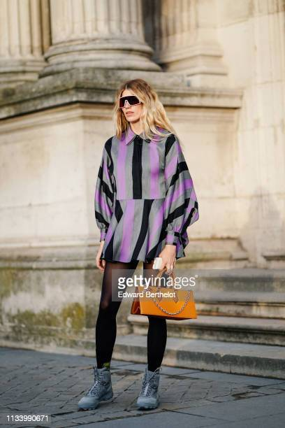 Veronika Heilbrunner wears sunglasses a purple and black striped pleated dress sneakers a brown bag outside Louis Vuitton during Paris Fashion Week...