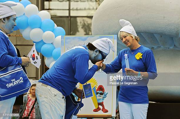 Veronique Culliford the daughter of creator of The Smurfs cartoonist Peyo is being hand kissed by a Smurf Ambassador as she hands certificates of...