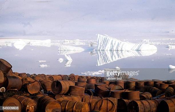 verrostete Ölfässer vor Eisbergen auf einer Insel in FranzJosefLand im nördlichen Eismeer 1996
