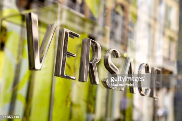 versace store sign in milan - versace designer label stock photos and pictures