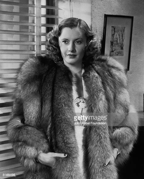 Versatile American screen actress Barbara Stanwyck wearing a lavish fur coat