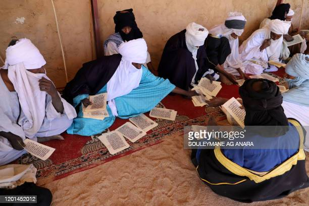 Verses of the Quran are passed along during a prayer at a local mosque in the Iferouane region Niger on February 14 while a Touareg caravan stops en...