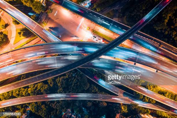 vertical aerial view of city overpass by drone at night - interchange stock pictures, royalty-free photos & images