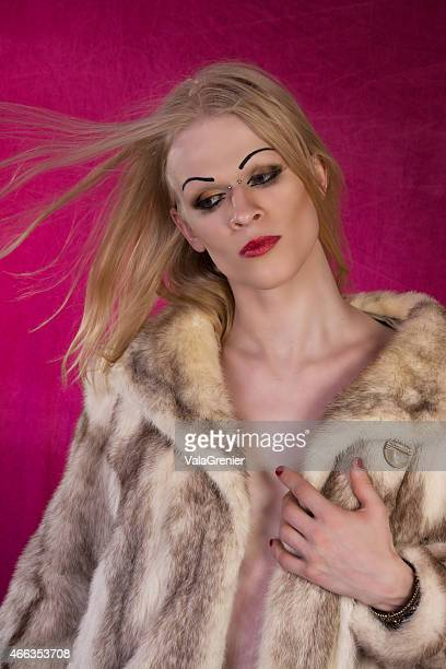 Vertical colour image of Transwoman in fur coat, hair blowing.