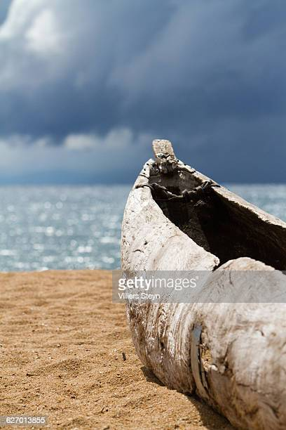 A vertical, cropped, close up, colour photograph of the front portion of a rustic, hand-crafted canoe resting on the sand beside Lake Malawi, with dark clouds gathering overhead in Malawi, Southern Africa.