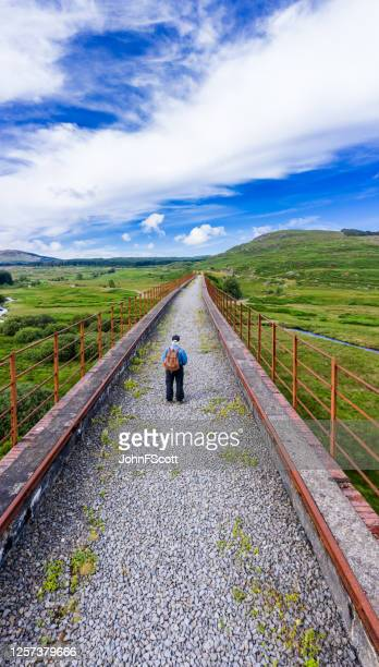 vertical high angle view of an active senior man on a disused railway viaduct in the scottish countryside - johnfscott stock pictures, royalty-free photos & images