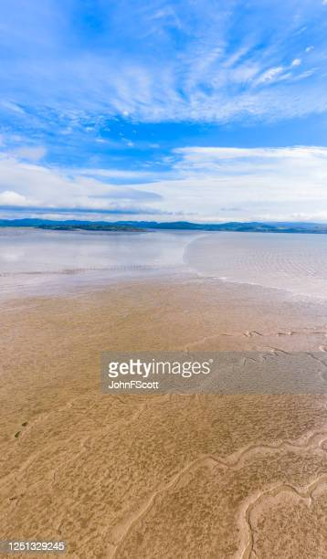 vertical panoramic view of sand as the tide comes in on a bright sunny morning in south west scotland - johnfscott stock pictures, royalty-free photos & images