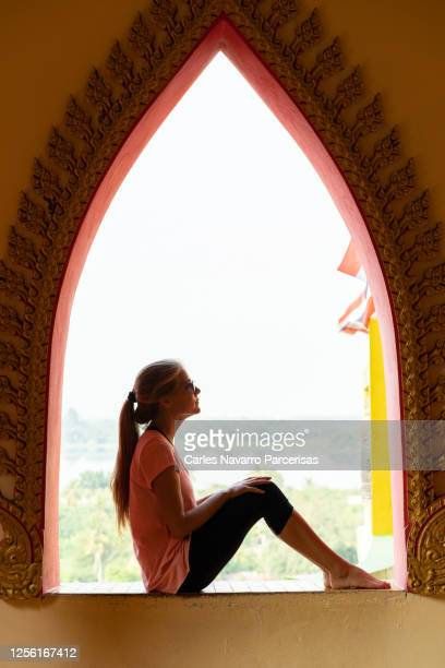 vertical photo of a profile of blonde woman sitting in the middle of an arch of a window in a buddhist temple with the views of a village and mountains in the background - frau beine breit stock-fotos und bilder