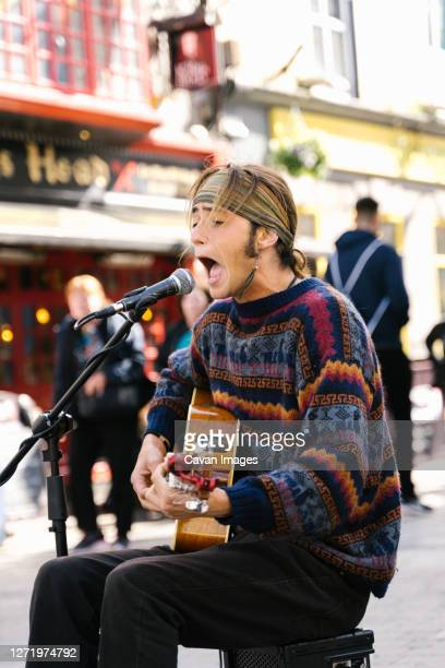 vertical photo of a young man singing while playing guitar in the street - singer stock pictures, royalty-free photos & images
