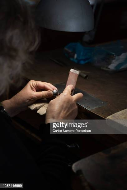 vertical photo of the selective focus on the hands of an elderly woman sanding a silver ball in a jewelry workshop - artists equity ball stock pictures, royalty-free photos & images