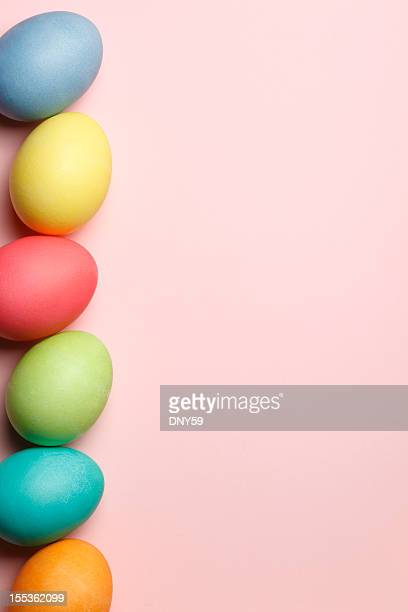 Vertical row of Easter eggs on pink background