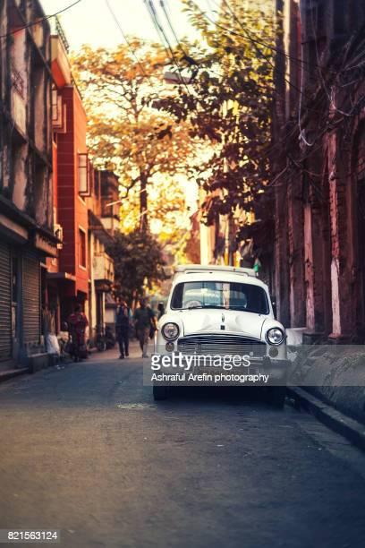Vertical shot of a White car in street of Kolkata India