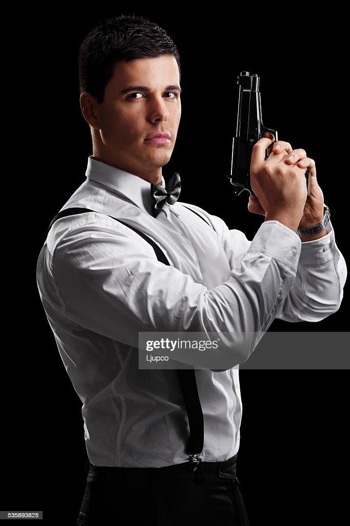 Vertical shot of an elegant man holding a gun : Stock Photo