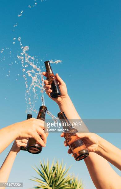 vertical shot of people lifting and tossing bottle showing of celebration - men friends beer outside stock pictures, royalty-free photos & images