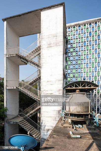 Vertical view of dramatic concrete stairs on east elevation, the service side of the building. The coffin shaped concrete panels are infilled with...