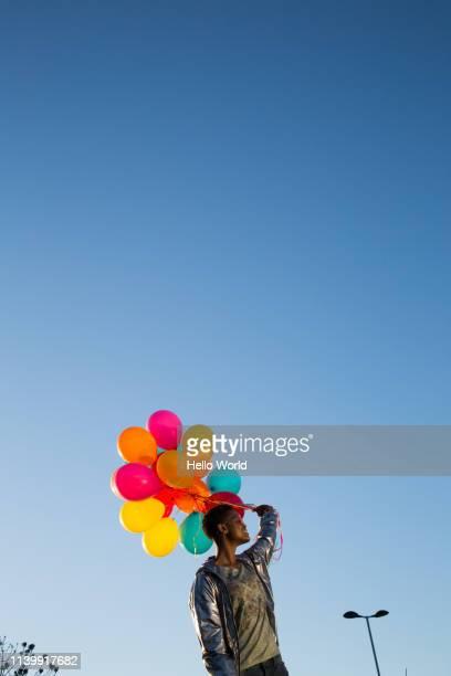 vertical view of young woman holding colorful balloons on blue sky background - loslassen aktivitäten und sport stock-fotos und bilder