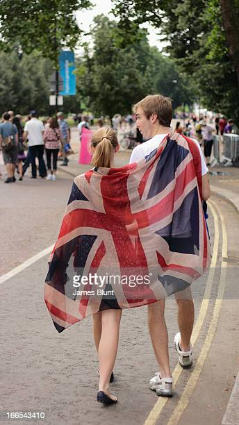 Verticle image of man and woman walking wrapped in a british union jack flag in Hyde Park, during the London 2012 Olympics. In the background there...