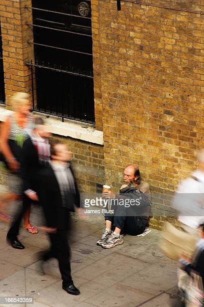 CONTENT] Verticle image of people walking past a man sitting in the street The people are blurred by a slow shutter speed as they pass the man's...