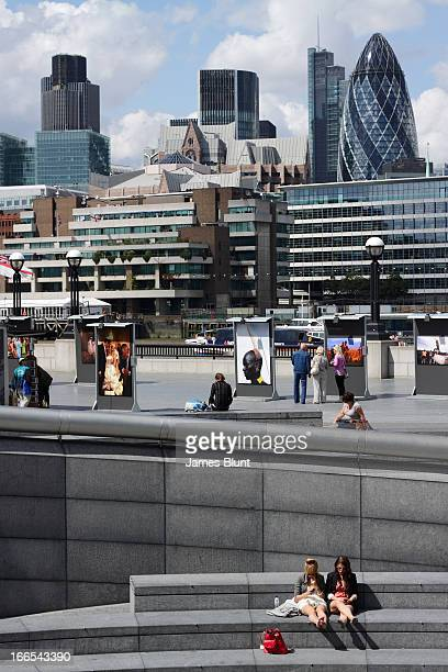 Verticle image of two women sitting in bright sunshine near City Hall, with the Gherkin in the background. Behind the sitting women, there is an...