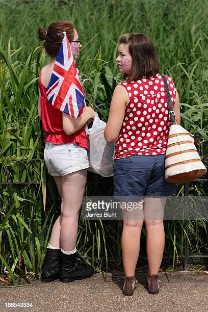 Verticle image of two young women with british face paint on their cheeks during the London 2012 Olympics. There is a green background, with one of...