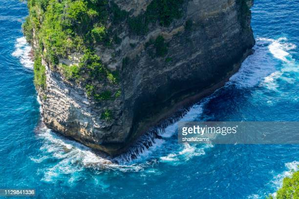 Vertiginous, swirling foamy water waves at the ocean photographed from above cliff.