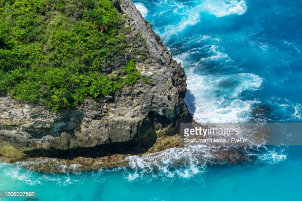 vertiginous, swirling foamy water waves at the ocean photographed from above cliff. - shaifulzamri stock pictures, royalty-free photos & images