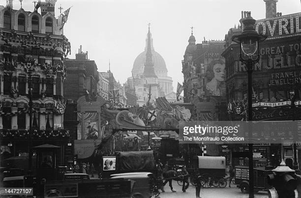 Very busy London street scene full of horsedrawn carts and carriages and motor vehicles at Ludgate Circus with buildings and The King Lud public...
