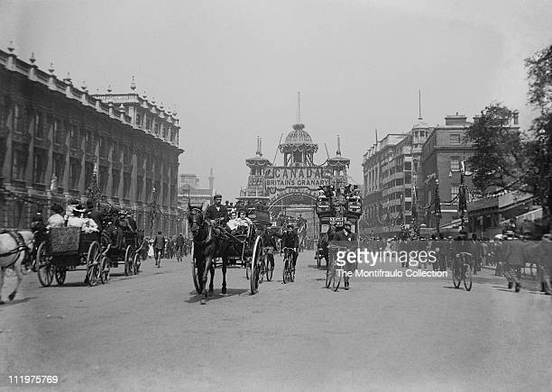 Very busy street scene with lots of people many horse driven buses and carriages The Canadian Arch Whitehall London England decorated to celebrate...