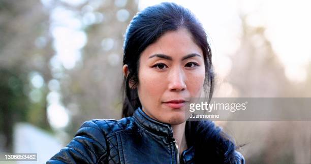 very concerned pensive serious unemployed asian mid adult woman looking at the camera - korean ethnicity stock pictures, royalty-free photos & images
