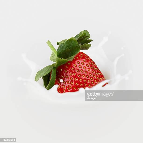 Very delicious Strawberry falling into fresh milk splashing