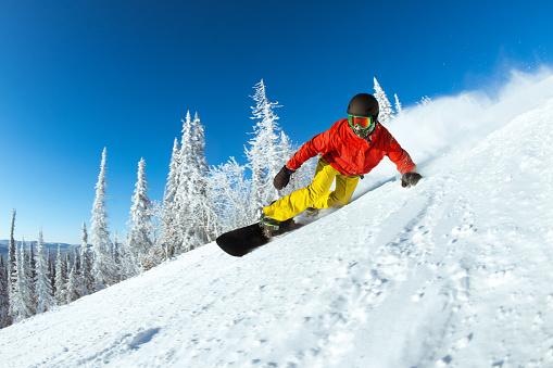 Very fast snowboarder slides at ski slope 910031152