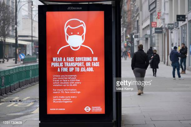 Very few people out along the pavements of Oxford Street where bus advertising posters advise people to wear face masks as the national coronavirus...