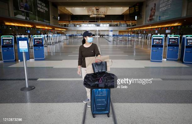 Very few travelers in the Tom Bradley International Terminal, Los Angeles International Airport which is now requiring travelers to wear face...