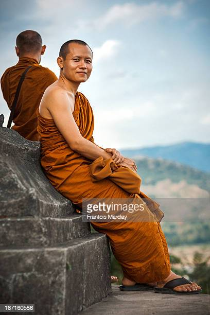 CONTENT] Very friendly and smiling Thai Buddhist monk on a pilgrimage trip to the temples of Luang Prabang Sitting against a statue found on top of...