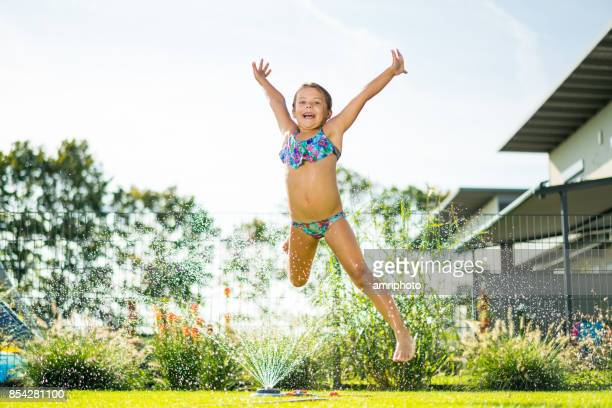 very happy 6 years old girl jumping over water in garden