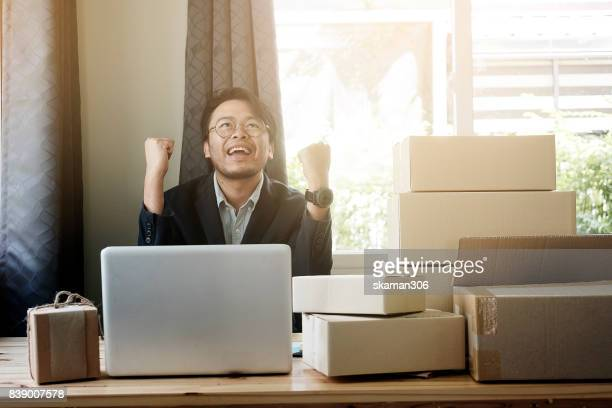 very happy asian business man holding tablet  and package of online shopping with laptop computer with Packaged to be shipped Global shipping and delivery