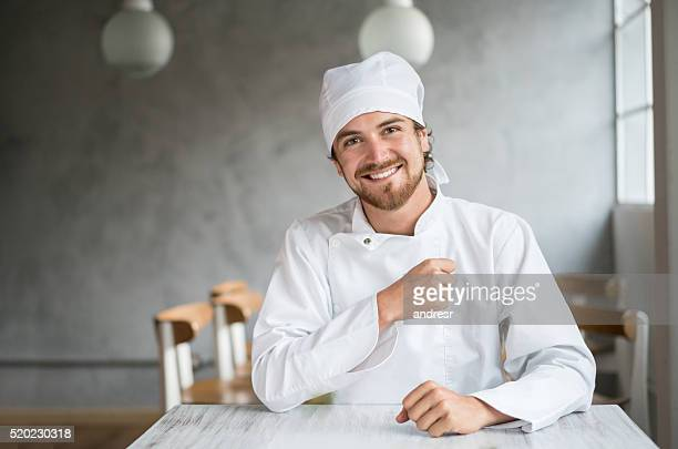 Very happy chef sitting at a table