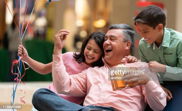 very happy grandfather celebrating father's day with his grandchildren - fathers day stock pictures, royalty-free photos & images