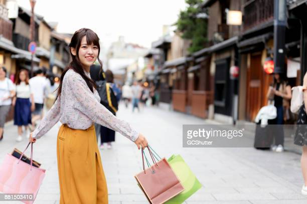 very happy japanese girl looking towards the camera with her bags in hand. - japanese girl stock photos and pictures