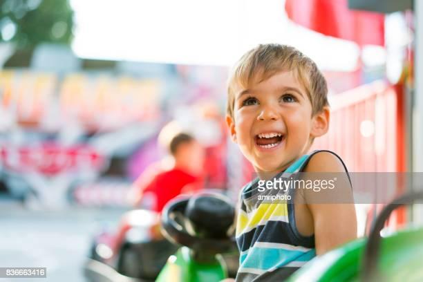 夏に遊園地で非常に満足の litlle 少年 - 遊園地の乗り物 ストックフォトと画像
