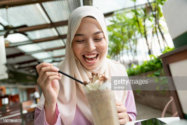 very happy muslim woman eating an ice cream at a cafeteria - malaysia stock pictures, royalty-free photos & images