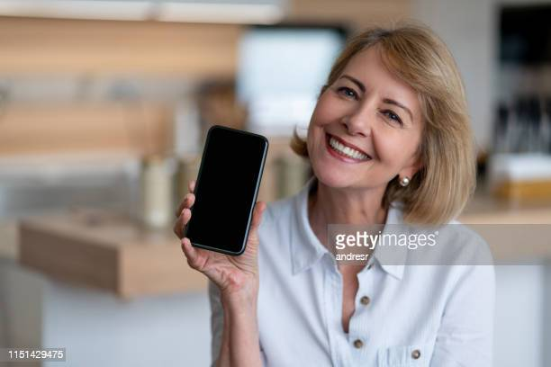 very happy senior woman at home using app on her cell phone - showing stock pictures, royalty-free photos & images
