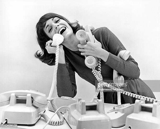 A very happy woman tries to answer four telephones at once United States circa 1968