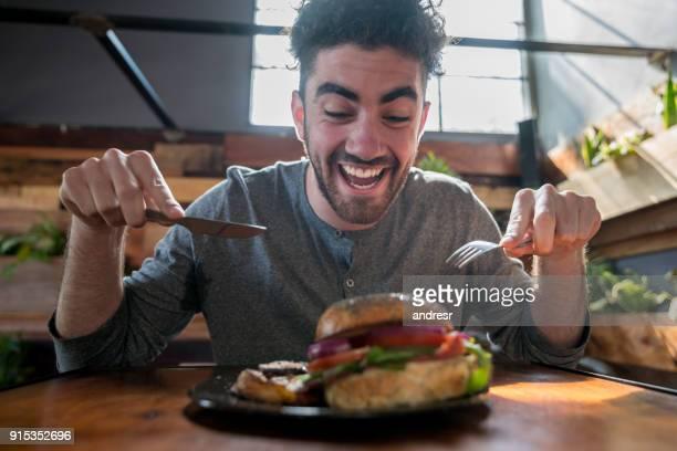 Zeer hongerig jongeman duik te nemen in zijn hamburger met bestek