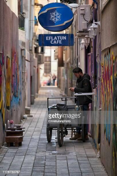a very narrow street with a man and a cartin the city. - emreturanphoto bildbanksfoton och bilder