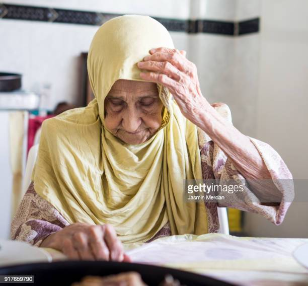 Very old Muslim woman at home eating lunch