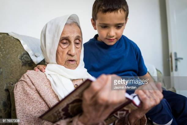 Very old Muslim woman at home reading with little boy