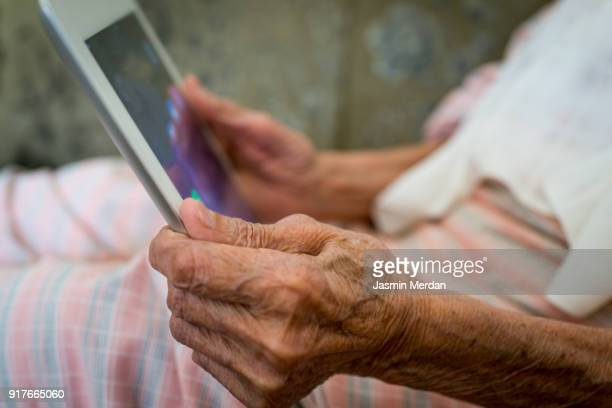 Very old Muslim woman at home using digital tablet