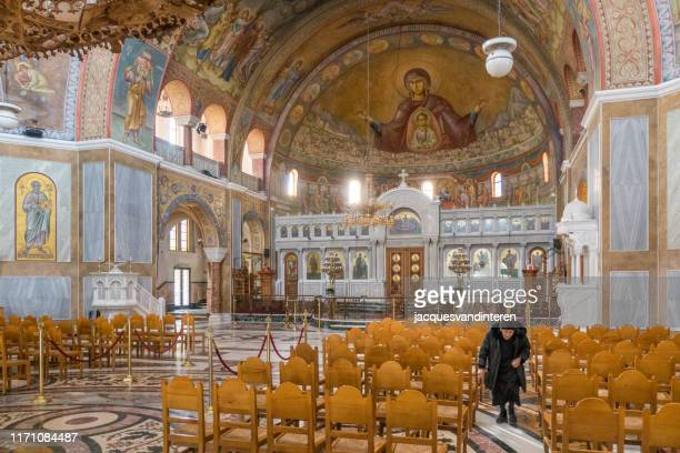 very old woman inside st andrew's cathedral or cathedral church of saint andrew (greek orthodox basilica) in patras, peloponnese, greece - greek orthodoxy stock pictures, royalty-free photos & images