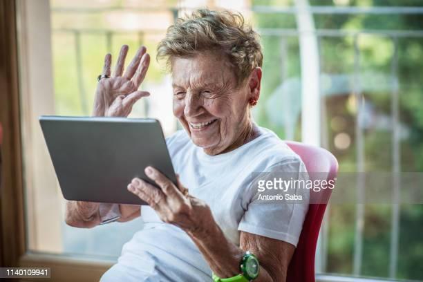 a very senior woman using digital tablet on apartment balcony - seniorinnen stock-fotos und bilder